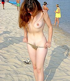 Naughty teen shows off her privates on the sand
